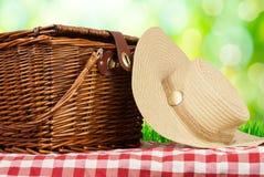 在桌和帽子上的野餐篮子 免版税库存照片