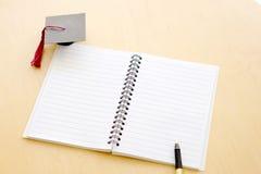 在桌和毕业盖帽上的空白的笔记本 库存照片
