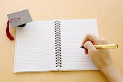 在桌和毕业盖帽上的空白的笔记本 免版税库存图片