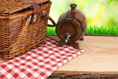 在桌和酒大桶油罐顶部角钢的野餐篮子 免版税库存图片