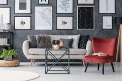 在桌和长沙发在现代公寓内部与画廊和植物旁边的红色椅子蒲团的 实际照片 免版税库存照片