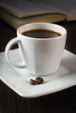 在桌和阅读书上的黑浓咖啡 免版税库存照片