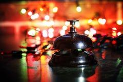 在桌和颜色光亮的诗歌选上的招待会响铃在背景 图库摄影