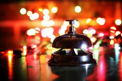 在桌和颜色光亮的诗歌选上的招待会响铃在背景 免版税库存图片