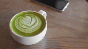 在桌咖啡馆商店的热的绿茶拿铁艺术 免版税库存图片