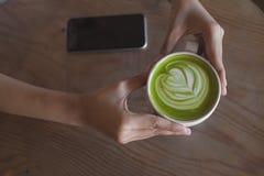 在桌咖啡馆商店的热的绿茶拿铁艺术 库存图片