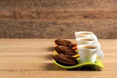 在桌安置的三个杯子新鲜的咖啡和巧克力饼干 免版税库存照片