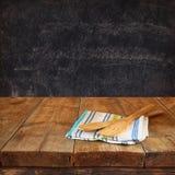 在桌布的厨房器物在反对黑板背景的木纹理桌上 免版税库存照片