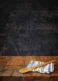在桌布的厨房器物在反对黑板背景的木纹理桌上 免版税库存图片