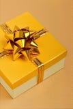 在桌布的金黄礼物盒 免版税库存图片