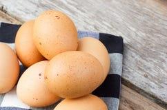 在桌布的鸡蛋在木桌 免版税库存照片