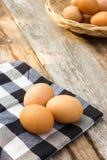 在桌布的鸡蛋在木桌 免版税图库摄影