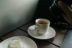 在桌木头的咖啡和使用照相机的人 免版税库存照片