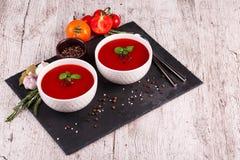 在桌背景的Gazpacho汤 蕃茄、大蒜、蓬蒿和胡椒一辣红色汤烹调的 库存图片