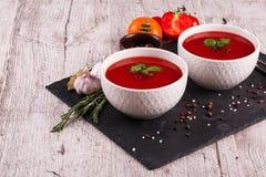 在桌背景的Gazpacho汤 蕃茄、大蒜、蓬蒿和胡椒一辣红色汤烹调的 免版税图库摄影