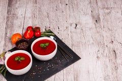 在桌背景的Gazpacho汤 蕃茄、大蒜、蓬蒿和胡椒一辣红色汤烹调的 免版税库存图片