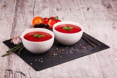 在桌背景的Gazpacho汤 蕃茄、大蒜、蓬蒿和胡椒一辣红色汤烹调的 库存照片
