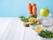 在桌芝麻菜青豆苹果计算机水蜂蜜薄脆饼干红萝卜拷贝空间的健康饮食食物 免版税库存图片