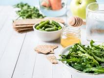 在桌芝麻菜青豆苹果计算机水蜂蜜薄脆饼干红萝卜拷贝空间的健康饮食食物 图库摄影