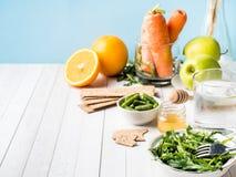 在桌芝麻菜青豆苹果计算机水蜂蜜薄脆饼干红萝卜橙色拷贝空间的健康饮食食物 库存照片