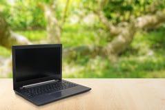 在桌迷离背景的计算机膝上型计算机与bokeh 库存图片