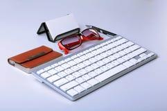 在桌面上的企业辅助部件:笔记本,日志,钢笔,玻璃 与迷离和软的焦点的宏指令 库存图片