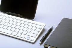 在桌面上的企业辅助部件:笔记本,日志,钢笔,玻璃 与迷离和软的焦点的宏指令 免版税库存图片