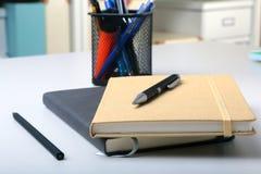 在桌面上的企业辅助部件:笔记本,日志,钢笔,玻璃 与迷离和软的焦点的宏指令 免版税库存照片