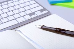 在桌面上的企业辅助部件:笔记本,日志,钢笔,玻璃 与迷离和软的焦点的宏指令 库存照片