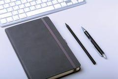 在桌面上的企业辅助部件:笔记本,日志,钢笔,玻璃 与迷离和软的焦点的宏指令 图库摄影