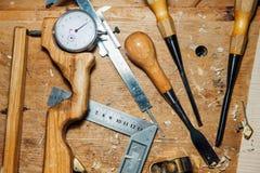 在桌面上的工具在车间 做小提琴 刨花和尘土,创造性的混乱 免版税库存图片