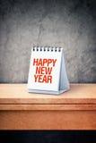 在桌面日历的新年快乐在办公室桌上 库存照片