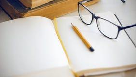 在桌面百科全书、笔记本、铅笔和玻璃的事 免版税图库摄影