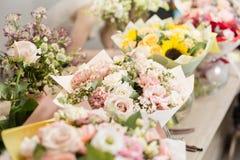 在桌,卖花人事务上的花束 不同的品种新鲜的春天花 背景配件箱发运英俊查出在服务白色工作者 花店概念 库存图片