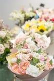 在桌,卖花人事务上的花束 不同的品种新鲜的春天花 背景配件箱发运英俊查出在服务白色工作者 花店概念 免版税库存照片