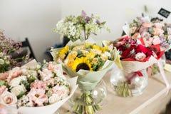 在桌,卖花人事务上的花束 不同的品种新鲜的春天花 背景配件箱发运英俊查出在服务白色工作者 花店概念 免版税库存图片