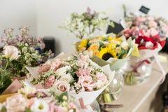 在桌,卖花人事务上的花束 不同的品种新鲜的春天花 背景配件箱发运英俊查出在服务白色工作者 花店概念 库存照片