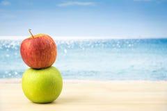 在桌,海滩背景上的绿色苹果和红色苹果 免版税库存照片