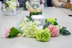 在桌,花的布置车间上的五颜六色的人造花 库存图片