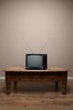 在桌黑屏上的老减速火箭的电视 库存照片
