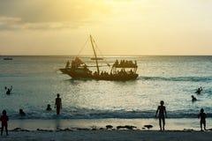 在桑给巴尔海滩附近的旅游船在日落 库存图片