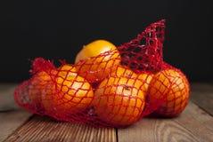 在桔子的柑橘水果蜜桔在塑料网兜包裹 没有塑料概念 包装不回收 塑料 Rusti 免版税库存照片