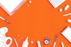 在桔子的被分类的办公室和学校白色文具 免版税库存图片