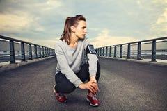 在桥梁休息的健身赛跑者 库存图片