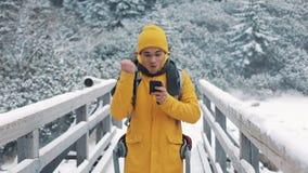 在桥梁和使用智能手机的一个年轻旅游身分 庆祝徒步旅行者读的喜讯看手机 股票录像