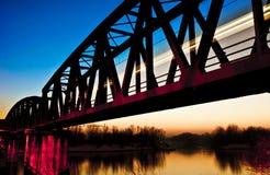 在桥梁在日落,克雷莫纳,意大利的火车 免版税库存图片