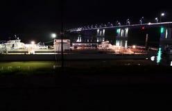在桥梁旁边的驳船在晚上 免版税库存图片