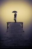 在桥梁的一把伞的保护的孤独的妇女 库存图片