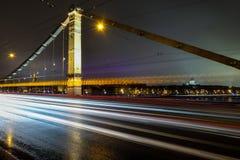 在桥梁的光足迹在晚上 库存图片