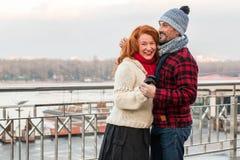 在桥梁的夫妇跳舞 拥抱近障碍的微笑的愉快的夫妇 美好的人爱每日走在城市 免版税库存图片